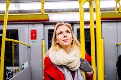 Schöne junge Frau im roten Mantel in der Untergrundbahn Stockbild