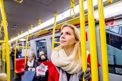 Schöne junge Frau im roten Mantel in der Untergrundbahn Lizenzfreie Stockbilder