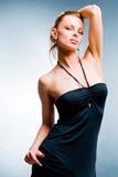 Schöne junge Frau im schwarzen Kleid. Im Studio Lizenzfreie Stockfotos
