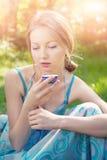 Schöne junge Frau im Sommerkleid, das eine Tasse Tee hält Lizenzfreie Stockfotos