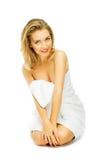 Schöne junge Frau im Tuch Terry sitzt Stockfotografie