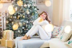 Schöne junge Frau im Weiß mit großen Weihnachtsgeschenken stockfoto