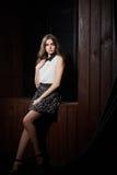Schöne junge Frau im weißen Hemd und in der schwarzen Rockaufstellung Stockbild