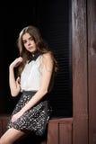 Schöne junge Frau im weißen Hemd und in der schwarzen Rockaufstellung Stockbilder