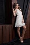 Schöne junge Frau im weißen Kleid, auf braunem Hintergrund Stockbild