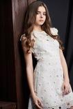 Schöne junge Frau im weißen Kleid, auf braunem Hintergrund Stockfoto
