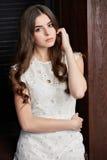 Schöne junge Frau im weißen Kleid, auf braunem Hintergrund Stockbilder
