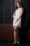 Schöne junge Frau im weißen Kleid, auf braunem Hintergrund Lizenzfreie Stockfotografie