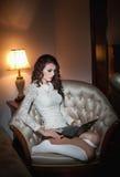 Schöne junge Frau im weißen Sitzen auf dem Sofa, das an Laptop in der Boudoirlandschaft arbeitet. Attraktives Brunettemädchen mit  Stockfotos