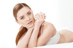 Schöne junge Frau im weißen Unterwäschelügen lokalisiert auf Weiß Stockfoto