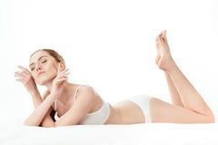 Schöne junge Frau im weißen Unterwäschelügen lokalisiert auf Weiß Stockfotografie
