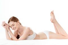 Schöne junge Frau im weißen Unterwäschelügen lokalisiert auf Weiß Lizenzfreie Stockbilder