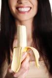 Schöne junge Frau isst Banane. lizenzfreie stockfotografie