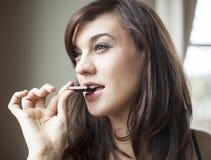 Schöne junge Frau isst Stück dunkle Schokolade stockbild