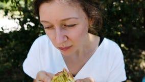 Schöne junge Frau isst und genießt reife Feigen in einer Sommerparknahaufnahme, Zeitlupe stock video