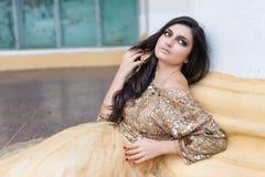 Schöne junge Frau ist, berührend sitzend und ihr Haar Stockfoto