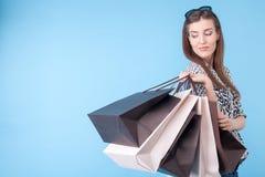 Schöne junge Frau ist gehender Einkauf mit Freude Stockfotos