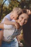 Schöne junge Frau macht ihre zurück kleine Schwester weiter Stockbilder