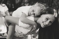 Schöne junge Frau macht ihre zurück kleine Schwester weiter Stockbild