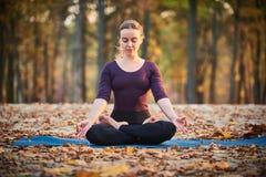 Schöne junge Frau meditiert in Yoga asana Padmasana - Lotus-Haltung auf der hölzernen Plattform im Herbstpark stockfotografie