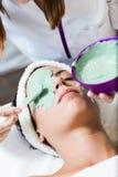 Schöne junge Frau mit antiaging Gesichtsmaske im Badekurort lizenzfreies stockfoto