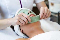 Schöne junge Frau mit antiaging Gesichtsmaske im Badekurort lizenzfreies stockbild