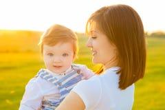Schöne junge Frau mit Baby auf dem Sommersonnenuntergang Stockbilder