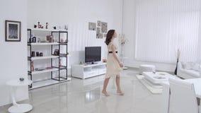Schöne junge Frau mit bloßen Füßen und einem beige Kleid zieht in den Innenraum im Wohnzimmer in der Zeitlupe um reizvoll stock video
