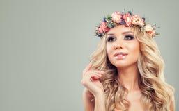 Schöne junge Frau mit Blumen, blonde gelockte Frisur Lizenzfreies Stockfoto