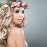 Schöne junge Frau mit Blumen-Frisur Lizenzfreie Stockbilder