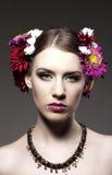 Schöne junge Frau mit bunten Blumen im hai Stockbild