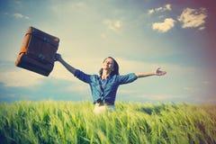 Schöne junge Frau mit dem braunen Koffer, der in der Mitte steht Lizenzfreies Stockbild