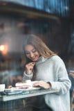 Schöne junge Frau mit dem braunen langen Haar, das im Café, drin sitzt lizenzfreie stockfotografie