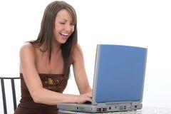 Schöne junge Frau mit dem Computer-Lachen Stockfotos