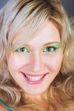 Schöne junge Frau mit dem Lächeln der grünen Augen Stockfotografie
