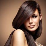 Schöne junge Frau mit dem lang geraden braunen Haar Lizenzfreie Stockfotografie