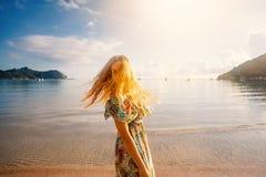 Schöne junge Frau mit dem langen blonden Haar auf einem Hintergrund von tr stockfotografie