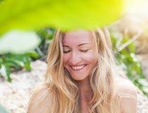 Schöne junge Frau mit dem langen blonden Haar lächelnd mit geschlossenem e lizenzfreie stockbilder