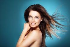 Schöne junge Frau mit dem langen braunen Fliegenhaar auf blauem backg lizenzfreie stockfotografie