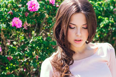 Schöne junge Frau mit dem langen gelockten Haar, das nahe Rosen in einem Garten aufwirft Das Konzept der Parfümwerbung Stockfotos