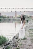 Schöne junge Frau mit dem langen gelockten Haar gekleidet im boho Artkleid, das nahe See aufwirft Lizenzfreie Stockfotografie