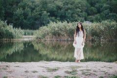 Schöne junge Frau mit dem langen gelockten Haar gekleidet im boho Artkleid, das nahe See aufwirft Stockbilder