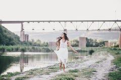 Schöne junge Frau mit dem langen gelockten Haar gekleidet im boho Artkleid, das nahe See aufwirft Lizenzfreies Stockfoto