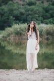 Schöne junge Frau mit dem langen gelockten Haar gekleidet im boho Artkleid, das nahe See aufwirft Lizenzfreies Stockbild