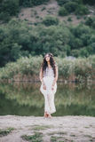 Schöne junge Frau mit dem langen gelockten Haar gekleidet im boho Artkleid, das nahe See aufwirft Stockbild