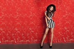 Schöne junge Frau mit dem langen gelockten Haar im schwarzen Hut und in gestreiftem Kleid auf rotem Hintergrund Lizenzfreie Stockbilder