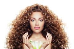 Schöne junge Frau mit dem langen gelockten Haar, klarer Haut und der Lilienblume lokalisiert auf Weiß stockfotografie