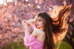 Schöne junge Frau mit dem langen gesunden Schlaghaar, das in Blütenpark bei Sonnenuntergang läuft lizenzfreie stockfotografie