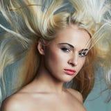 Schöne junge Frau mit dem langen Haar auf blauem Hintergrund Blondes Mädchen frisur Polnisch der Nägel mit dem nailfile Stockbild