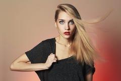 Schöne junge Frau mit dem langen Haar auf rotem Hintergrund Blondes Mädchen Stockfotografie